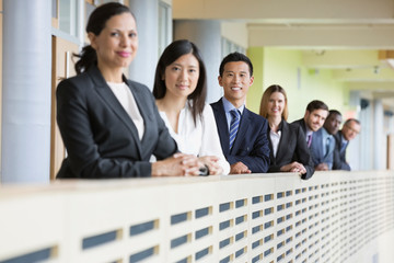 Portrait of confident business team standing by railing