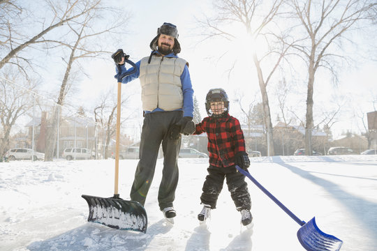 Portrait of father and son with snow shovels on ice rink