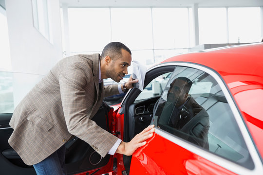 Man looking inside car in car dealership showroom