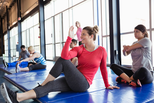Group of people stretching on mat in fitness center