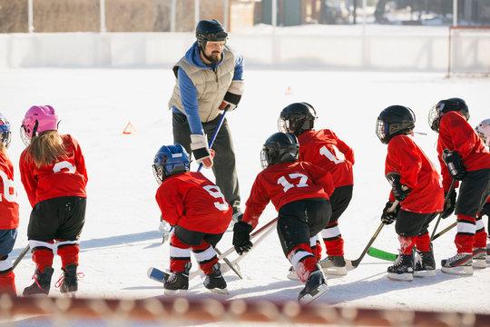 Coach instructing ice hockey team on rink