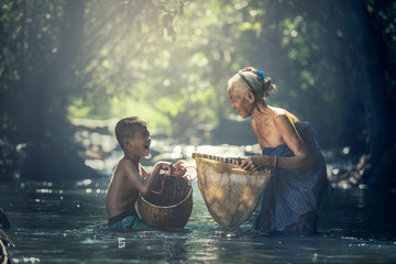 Asian Grandmother and her child are fishing in the creek at countryside of Thailand Fototapete