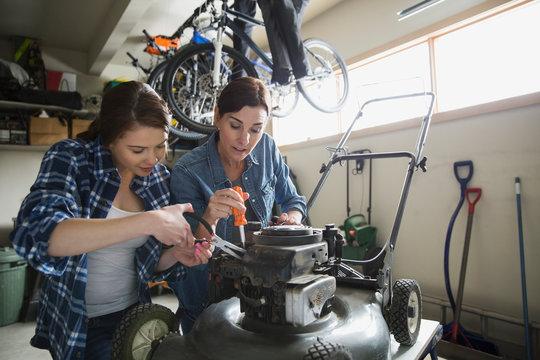Mother and daughter repairing lawn mower in garage