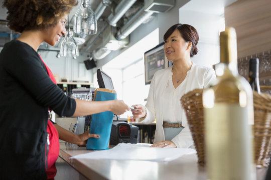 Cashier taking customer credit card in wine store