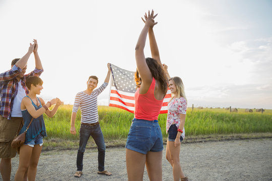 Friends holding up an American flag outdoors