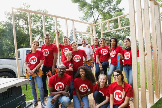 Portrait of smiling volunteers at construction frame