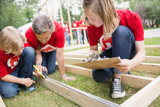 Volunteers measuring construction frame with tape measure