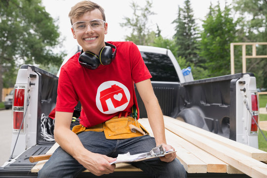 Portrait of smiling volunteer with clipboard on tailgate