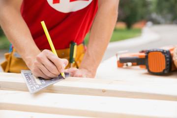 Volunteer marking wood with pencil