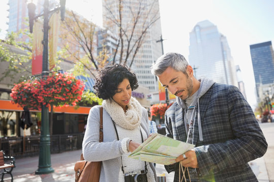 Couple looking at map on city street
