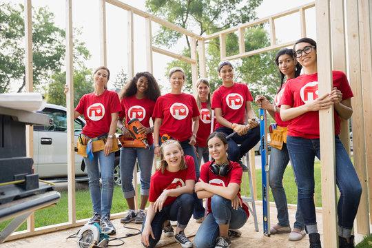 Portrait of smiling female volunteers at construction frame
