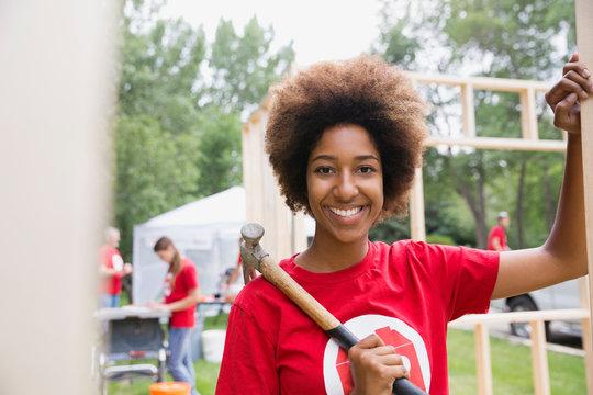 Portrait of confident volunteer at construction frame