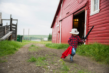 Boy with sword running outside barn