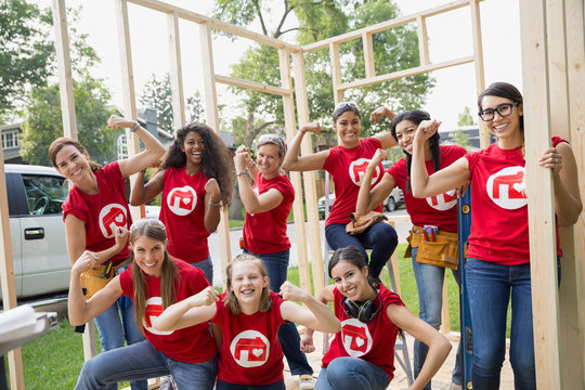 Female volunteers flexing muscles at construction frame