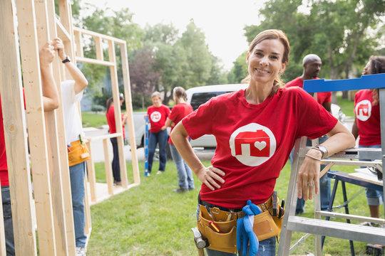 Portrait of confident volunteer leaning on ladder