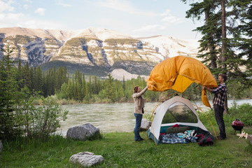 Couple assembling tent at campsite near mountains