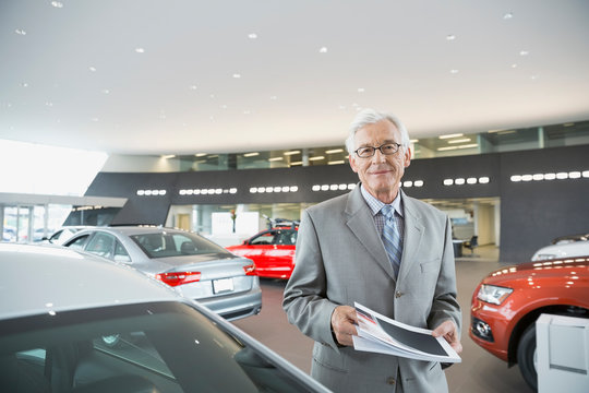 Confident man with brochure in car dealership showroom