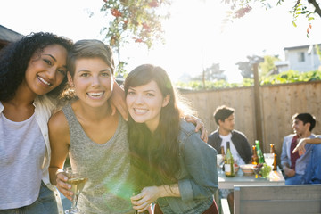 Portrait of smiling friends drinking at backyard barbecue