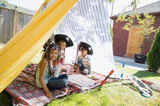Portrait of children playing pirates in backyard fort