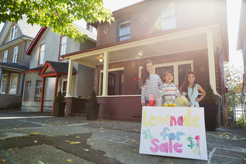Brother and sisters at lemonade stand outside house