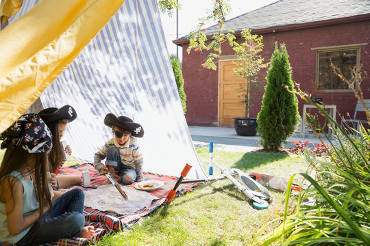 Brother and sisters playing pirates in backyard fort
