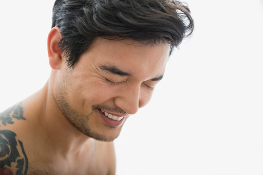 Bare chested man laughing with eyes closed