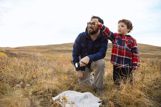 Father and son with treasure map in field