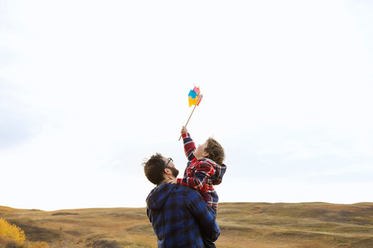 Father holding son with pinwheel in rural field