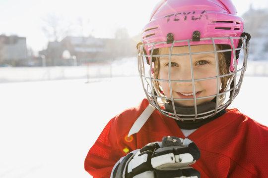 Portrait of smiling girl in ice hockey uniform