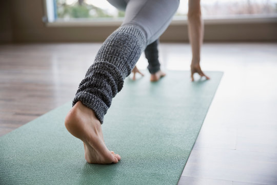 Woman practicing yoga in lunge pose on mat