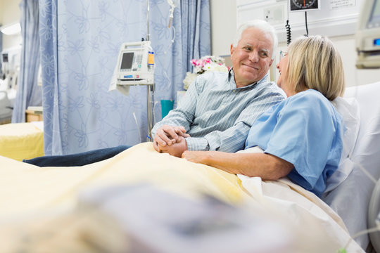 Husband and wife holding hands in hospital bed