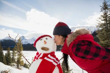 Woman kissing snowman below mountains