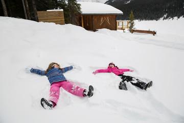 Girls making snow angels in snowy field