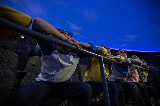 Students in 3D glasses enjoying planetarium show