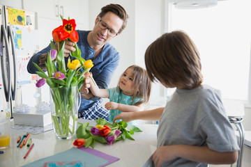 Father and children arranging tulip bouquet in kitchen