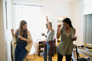 Friends drinking wine and dancing in living room