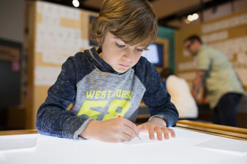 Boy tracing on light table at science center