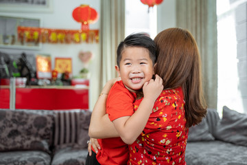Smiling asian little boy embracing her mother.Celebration of Lunar New Year with family