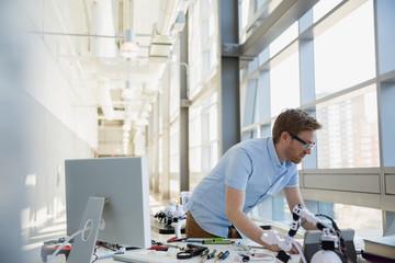 Engineer working at desk with robotics