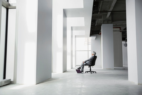 Pensive businesswoman sitting in chair in empty office