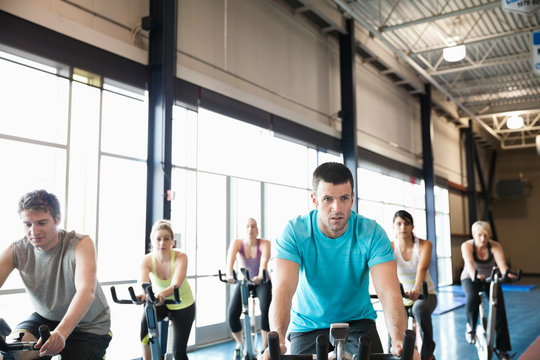 People exercising on stationary bikes in fitness class
