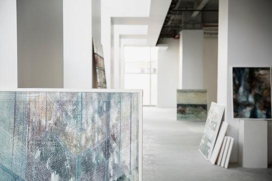 Paintings leaning against walls in art gallery