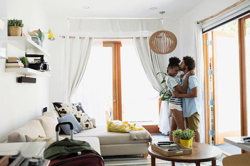 Couple hugging and kissing vacation house living room