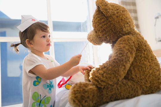 Girl in costume playing nurse to teddy bear