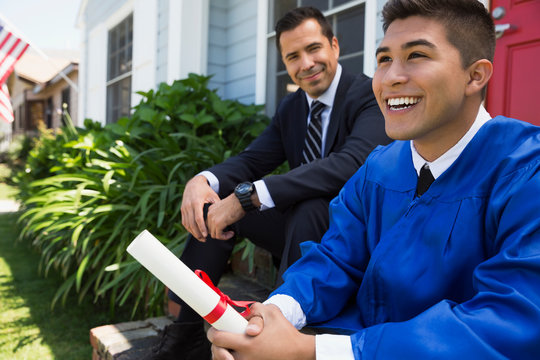 Father and graduate son with diploma front stoop