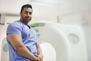Portrait of mid adult male radiologist in front of CAT scan machine