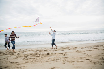 Friends flying a kite on beach