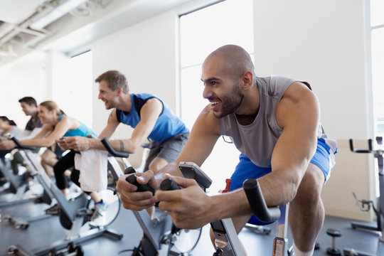 Smiling man enjoying spin class stationary bike gym