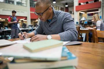 College student studying at table in library