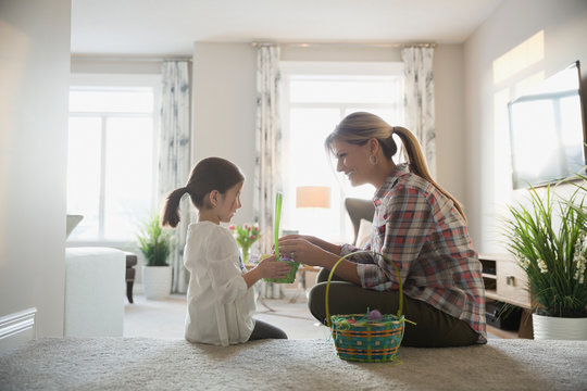 Mother and daughter counting Easter eggs at home